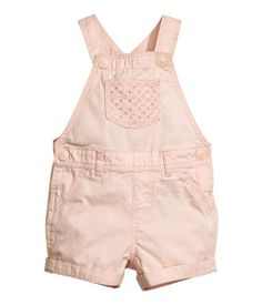 Powder pink. Bib overall shorts in soft, washed denim. Adjustable suspenders with snap fasteners at top. Bib pocket, seam at waist with belt loops, and mock