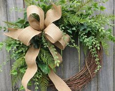 This year round wreath is the perfect accent for a front door or interior space. A wild wired burlap bow is surrounded by realistic ivy and fern. This wreaths fern and ivy have a light and airy feel where the grapevine base is visible in places. An antique white monogram provides a lovely accent. Approximate Diameter (tip to tip): 22 This wreath was made on a grapevine wreath measuring approximately 18 Indoor/ Sheltered Outdoor Safe *Try to avoid exposing this wreath to lots of direct...