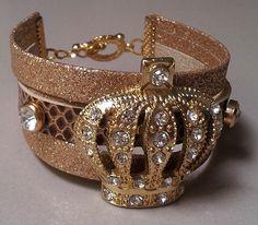 Linda pulseira em couro sintético com detalhes dourados, com coroa de rainha dourada e strass....