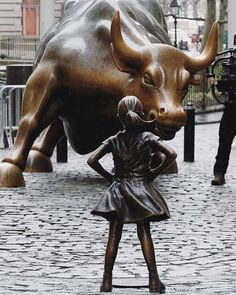 A Fearless Girl Cast in Bronze Stands In Proud Defiance Against the Famous Wall Street Bull