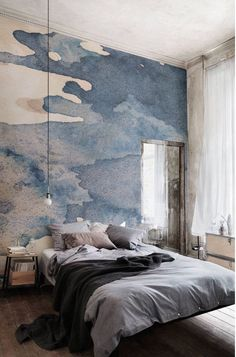 The mirror helps reflect light around the room, giving the illusion of another window. The mural on the wall is also an illusory light source, and the blue hues are echoed in the bedding.
