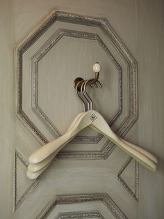 Limed oak hangers with pewter monogram, cloak closet in NY apartment of Howard Slatkin