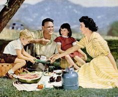 "Family picnic, 1951. - They were probably traveling. There weren't that many roadside restaurants to provide food, so people took their own food and stopped at a pretty place or at one of the roadside parks set up for that purpose. The parks just had concrete picnic tables and trash cans usually - all you needed to have a place to eat. Not much stuffing your mouth with fast food as you hurried to ""make time"". Sigh."
