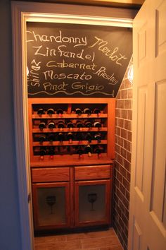 Wine closet. A great way to utilize the under the stairs space! The wooden panels were taken out of the vanity and replaced by glass which we frosted after creating the wine glass image. Wall and floor tiles from Menards and chalkboard paint.