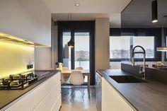 Una cocina moderna que integra una zona de comedor para el día a día.  Combinan a la perfección blancos y negros junto con la mesa de madera reciclada de estilo nórdico.
