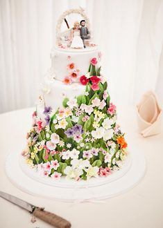 want a garden style cake? here's an inspiration model. a floral decoration with lots of colour, with incorporated daisies and butterflies, scattered flowers like a waterfall effect descending down the tiers merging into a base full of floral magic.  Gloucestershire country wedding blog with Joanna Bongard Photography (40)