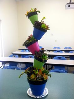 """A tower of """"tipsy pots"""" filled with beautiful succulents."""