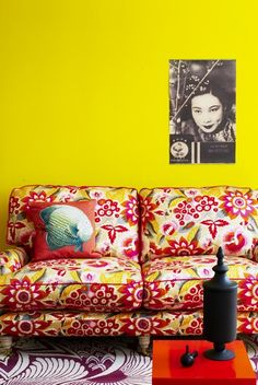 Eclectic boho living space - love the bright yellow wall, vintage print and kitschy couch.