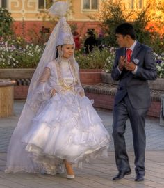 Brides in Kazahkstan wear an elaborate dress and a cone-shaped hat with lots of tulle. ~