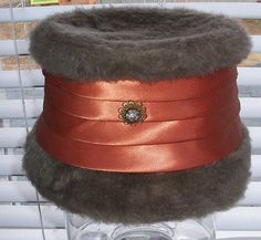 1920's Womens Union Made Hat Fur  4 tier banding around the hat.  Not a true orange, very muted.  Ornate metal piece on front with faux diamond stone.  faux fur.  Champagne beige in color.  Union Made with numbers 211900.