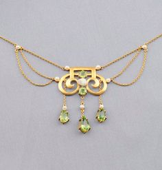 Art Nouveau 14kt Gold, Peridot, and Freshwater Pearl Pendant Necklace, the scrolling form with flexible fringe set with circular and pear-cut peridot, pearl highlights, flanked by festoons of delicate trace link chain, lg. 14 3/8 in.