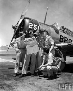British pilots in training read a newspaper account of the D-Day Allied invasion…