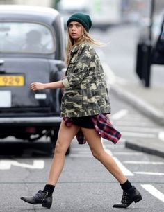 model street style: Cara Delevigne in camo coat, plaid shirt, booties and a cap