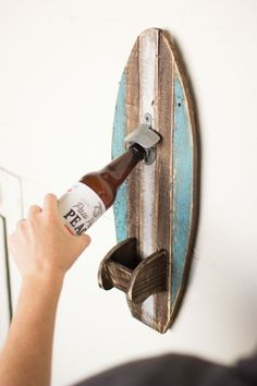 Rustic with a striped Blue , white, and natural finish, this playful wooden surfboard is ready to catch more than just a wave! With its metal bottle opener attachment and wooden fin bottle cap catcher