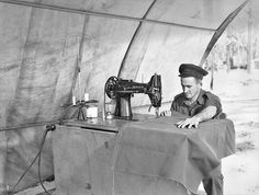 """History in Photos: Oz at War. Craftsman A R Bennett, motor trimmer of the 110th Brigade  Workshop, Australian Electrical and Mechanical Engineers, using  a heavy duty """"Singer"""" sewing machine to stitch canvas bags, May 1944"""