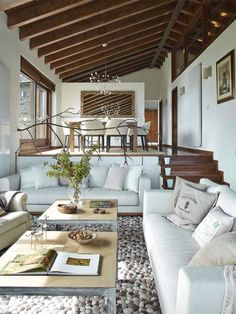 Modern rustic interior with wooden ceiling beams, pale blue sofas and pebbled rug by Deu i Deu