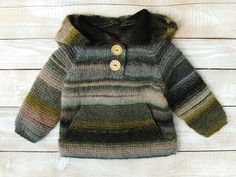This hoodie will fit baby boys or girls from 12 to 18 months.  Hand knitted from soft wool blend yarn (53% wool/47% acrylic), this warm olive green striped hoodie features wooden buttons, a front pocket and a large, over-sized hood. Perfect shower or birthday gift.  Sweater measures 13 1/2 from shoulder to hem, 12 across chest, and 13 from neckline to cuff.  Machine wash, dry flat.