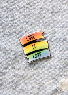 "Support LGBT rights with this colorful lapel pin. It features a rainbow banner with the quote, ""Love Is Love"". Each is handmade. - Shiny coating - Printed on durable plastic - Two tie tack pins on the"