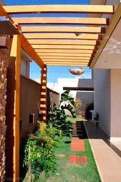 Prolongando a varanda, este pergolado está apoiado em uma viga metálica e na estrutura de madeira antes da divisa. Projeto de Fiorella Queiroz.