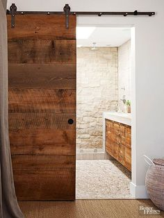 Organic surfaces unite to create a cohesive bathrooms design. An eye-catching barn door slides open to reveal a ruggedly outfitted bathroom featuring stacked-stone walls and a river-rock floor. Modern Farmhouse Bathroom, Rustic Bathrooms, Cottage Bathrooms, Chic Bathrooms, Bad Inspiration, Bathroom Inspiration, Bathroom Ideas, Small Bathroom, White Bathroom