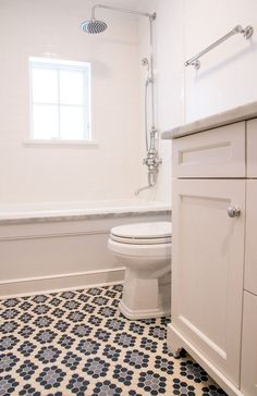 Colorful patterned mosaic tile floor in neutral bathroom  Lyon & Baehr