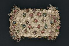 Muff, 1774-1793, London, Silk and silk fly fringe and chenille, wool batting. White silk covered by white silk ribbon and cord lattice studded with blue, salmon, purple chenille flowers, fly fringe and flowers at sides. MFA
