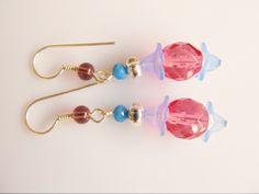 Oorbellen Lilly roze facet tsjechisch glas met blauwe bloemkelkjes acryl en blauw facet kristalglas rondel. oorhaken met rookkwarts met paarse ondertoon. geheel verzilverd. www.doloressieraden.nl