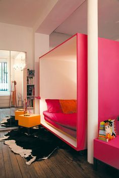 Pink plywood rolling cube bedroom for open plan living. Photo by Hervé Abbadie GENIUS // pink bed, pink bedroom, pink cube, rolling bed, pink and orange bedroom, orange nightstand, orange beside table, orange lamp, cowhide rug