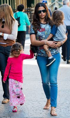 Family affair: She held her son Livingston, two, in her arms and her daughter Vida skipped along beside her