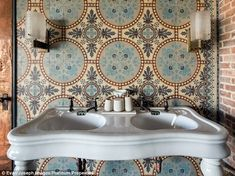 The bathroom features reclaimed 1930's floral patterned hand-cut blue stone tiles from Bel...