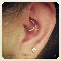 Daith and conch piercings by Bree featuring a white gold 5 gem ring and a genuine diamond set in white gold.