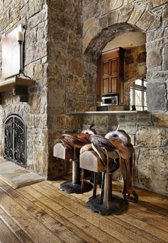Old saddles used as bar stools give this rustic interior a Western touch. Not a big fan of Western styles, but I love the rockwork and the wood floor.