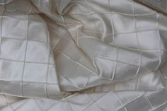Description Traditional Pintuck fabric with squares in a neutral ivory tone with a subtle sheen.