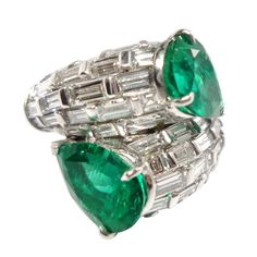 Colombian Emerald Diamond White Gold Ring. Handmade, of double snake design, with two pear shaped natural columbian emeralds and baguette-cut diamonds set in brick design. Friedrich, Germany, 2012