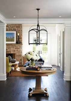 exposed brick, gorgeous molding, light and bright, round entry table, white flowers. I love it all.