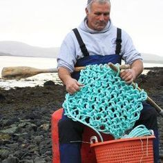 Hebridean fisherman using the oars of his coracle to knit a net.