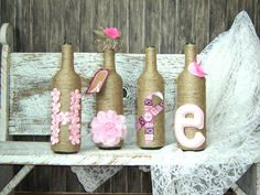 "Breast Cancer wine bottles vases. Spell ""hope"". Tightly wrapped in coated twine. Decorated with pink ribbon flowers, a pink lace flower, breast cancer ribbon with strength button. Also comes with a gift hang tag. 12"" tall. Insert flowers and use as a vase."