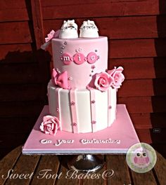 Christening cake for a girl pink with sugar paste baby shoes and sugar flowers