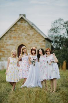 Fun, floral bridesmaid dresses in 50s style with white background and variety of colourful abstract floral prints, in yellows, pinks, purples and oranges.