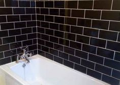 Bathroom Tiles Black stacked subway tile with dark grout + black wishbone chairs +