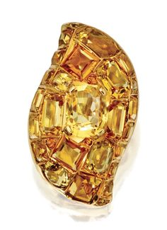 18 KARAT GOLD, YELLOW SAPPHIRE AND CITRINE BROOCH, SUZANNE BELPERRON, CIRCA 1945    Of bombé form set in the center with a cushion-shaped yellow sapphire, framed by square-cut, rectangular-shaped, round and oval citrines, maker's mark for Darde & Fils, French assay marks.