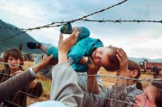 Agim Shala, 2 years old, catches his sock on a barbed wire as he is passed through a fence at the refugee camp run by the United Arab Emirates. Members of the Shala family are being reunited in Kukes, Albania, after fleeing Kosovo.  Carol Guzy.