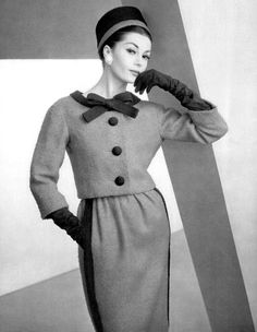 Model in red wool suit with short jacket and slighly gathered skirt, jacket and skirt trimmed in braid, by Christian Dior, photo by Pottier, 1959