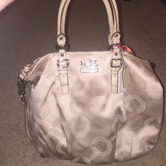 Authentic Coach No B1220-F15939 Authentic Coach bag Is a tanish/brown with a hint of metallic to its color. Bag has normal wear (used for about 6 months) with a mark on the exterior (pictures). Interior houses a large zipper pocket and two regular pockets. No blemishes on interior lining. Coach Bags Totes