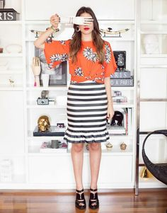 Mix & match de Amanda Cassou, co-founder do Gallerist, veste top laranja estampado e saia mídi listrada em preto e branco com babados.