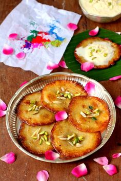 Malpua Rabdi (Indian Sweet). Popular at the Holi Festival. Fluffy pancakes dipped in sugar syrup and topped with sweetened milk & nuts - See recipe at: http://www.allaboutcuisines.com/recipe/malpua-rabdi-indian-sweet #Holi #Indian Sweets