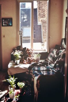 Cozy corner by a window with flannel sheets electric guitar green space plants vegetation indoor garden tiny apartment interior design boho Bohemia bohemian gypsy hippie vibes