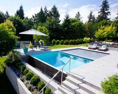 tumbonas negras bajo la sombrilla en el jardín con piscina