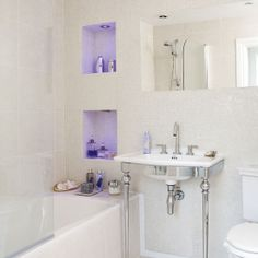 Recesses in the bathroom walls become designated places to store and display toiletries without taking up valuable space in the room. The colourful lighting adds a serene touch to the white scheme.