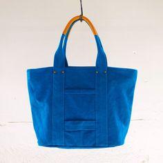 """Brand:JULY BY AKKA""""持つだけでお出かけが楽しくなる。倉敷帆布の虹色トートバッグ""""鮮やかな発色が魅力のAKKA EM STUDIO madeのトートバッグ。素材は、6号帆布を使用しており強度に優れています。こちらは、上品な青、リッチブルーです。濃厚なターコイズブルーのようなお色味です。あまり見かけることのないお色味なので、大人気カラーです!!!6号帆布という丈夫な素材を別注でオリジナルカラーに染めています。ふっくらとした凹凸のある生地表面も魅力的。持ち手の部分には手触りの良い牛革を使い、持ちやすく肩が疲れません。シンプルなコーディネートのワンポイントアクセントに、オシャレ感覚で持って頂けます。A4はもちろん、B4ファイルもすっぽり収納でき、お買い物や習い事、様々なシーンでご使用頂けます。バッグの正面には、ポケットがひとつ。便利な内ポケットも付いているので収納抜群です。脇に付いているホックをかければコンパクトサイズに変身します。使えば使い込むほど風合いが出て、お客様だけのオリジナルバッグに変身することでしょう。※こちらのトートバッグは、AKKA EM…"""